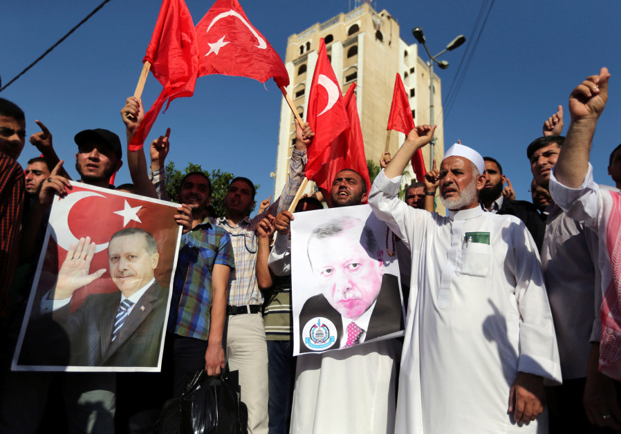HAMAS SUPPORTERS in Gaza hold posters of Turkish President Recep Tayyip Erdogan during a rall