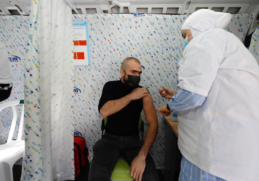 A resident of Tel-Aviv accepts gets COVID-19 vaccine shot on Tuesday February 16 2021 / GUY YECHIELI