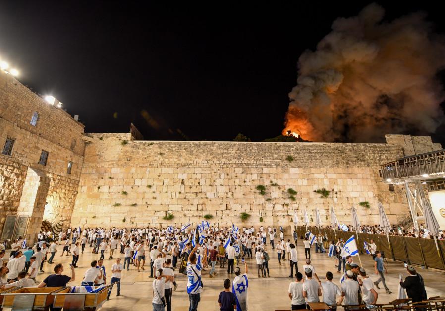 Israëli's vieren de dag van Jeruzalem bij de Westelijke Muur terwijl de brand op de achtergrond te zien is bij de al-Aqsa-moskee in de oude stad van Jeruzalem, 10 mei 2021. (Mendy Hechtman / Flash90)