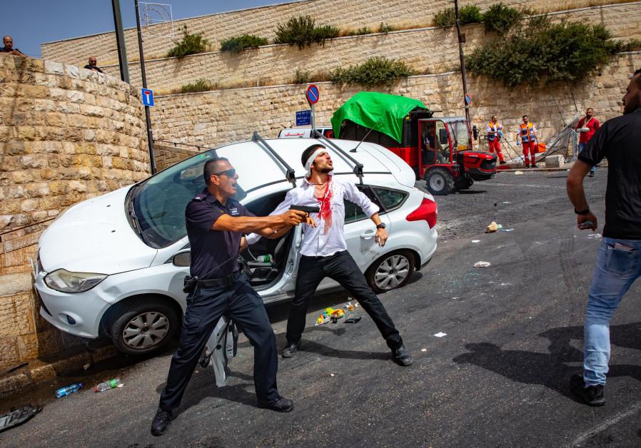 Een Israëlische politieagent houdt zijn wapen vast terwijl hij naast een gewonde Israëlische man staat nadat zijn auto crashte toen een menigte zijn auto bekogelde met stenen buiten de Oude Stad van Jeruzalem, 10 mei 2021 (Olivier Fitoussi / Flash90)