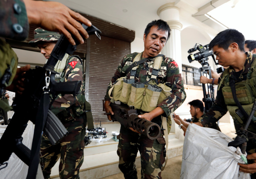 Philippines army soldiers store seized combat weapons in bags.