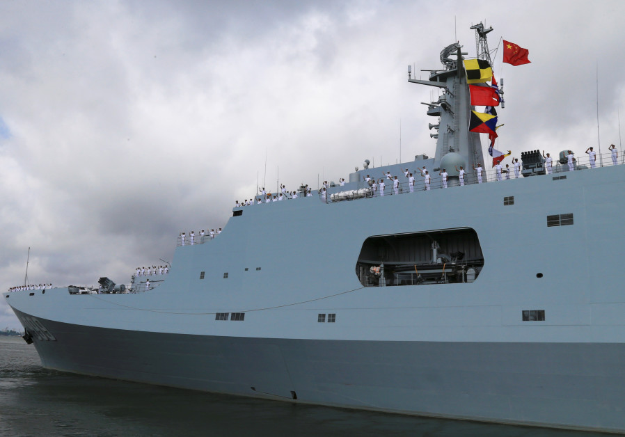 Soldiers of China's People's Liberation Army (PLA) salute from a ship sailing off from a military po