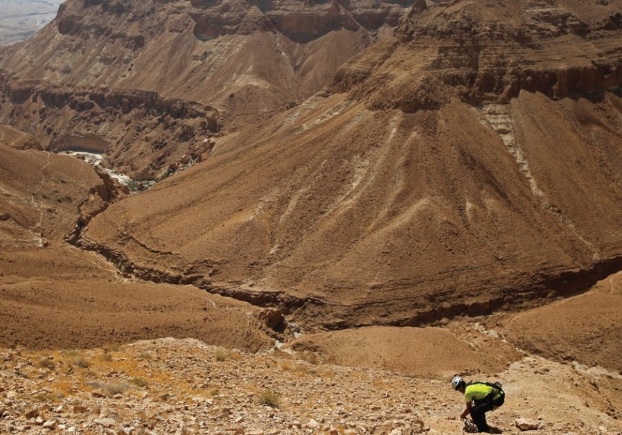 A MAN stands along a mountain range overlooking the Dead Sea.