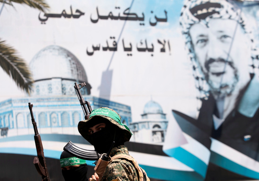 A poster depicting late Palestinian leader Yasser Arafat is seen as Hamas militants take part in a p
