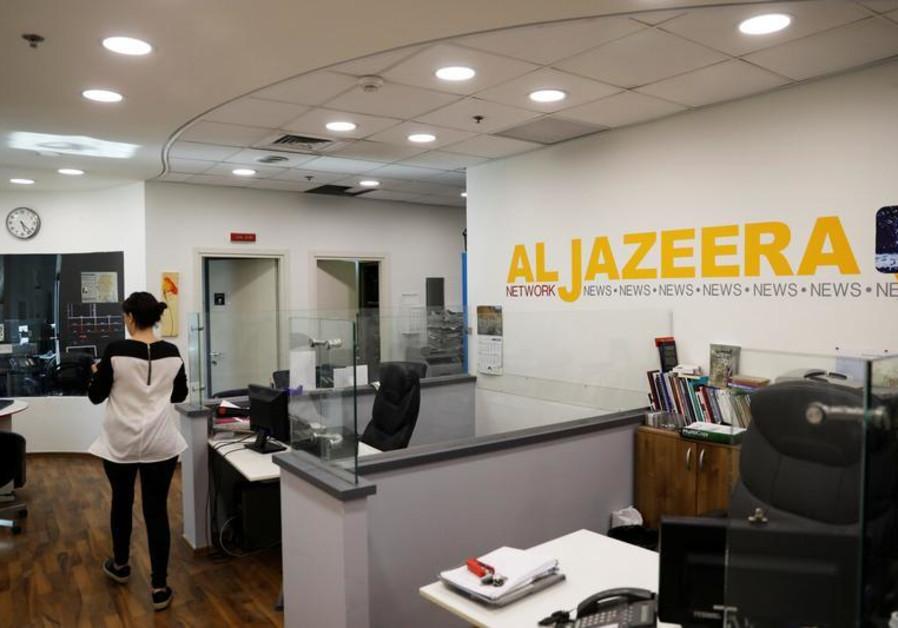 An employee walks inside an office of Qatar-based Al-Jazeera network in Jerusalem June 13, 2017.