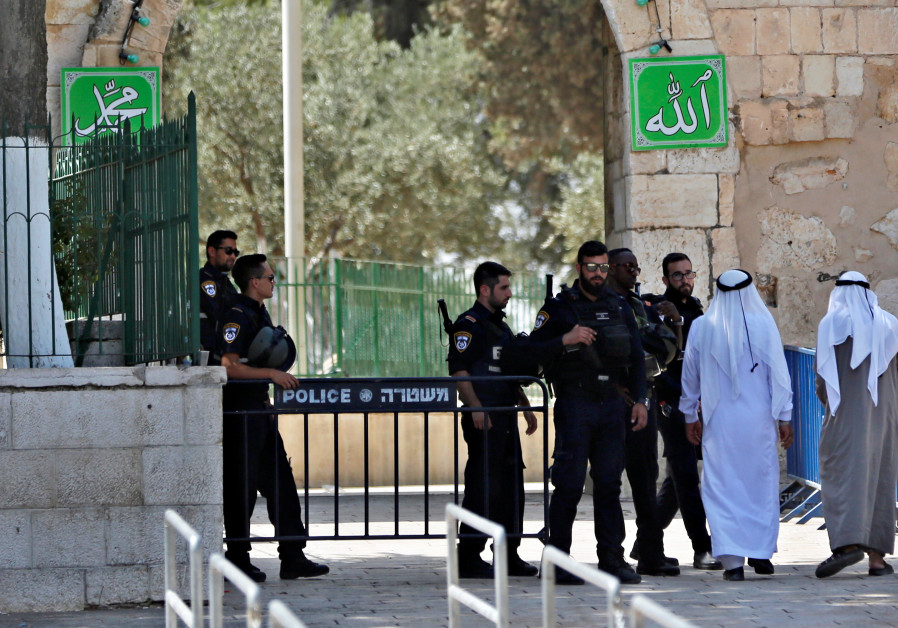 Palestinians walk next to Israeli security forces at the entrance of the compound known to Muslims a