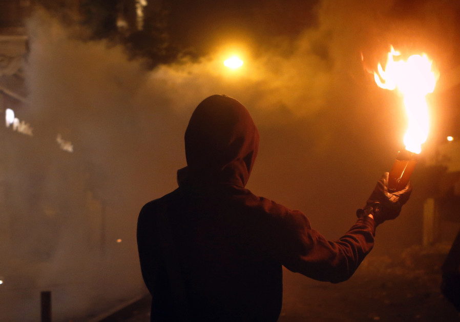 Hooded man holds flaming Molotov cocktail