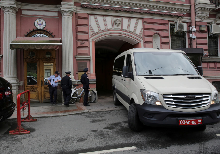 Security officers watch a consulate car entering the US consulate in St. Petersburg, Russia