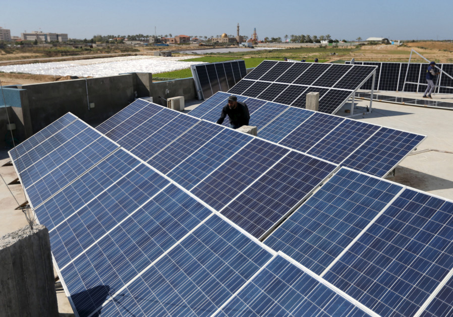 A worker installs solar panels on a roof in Gaza City