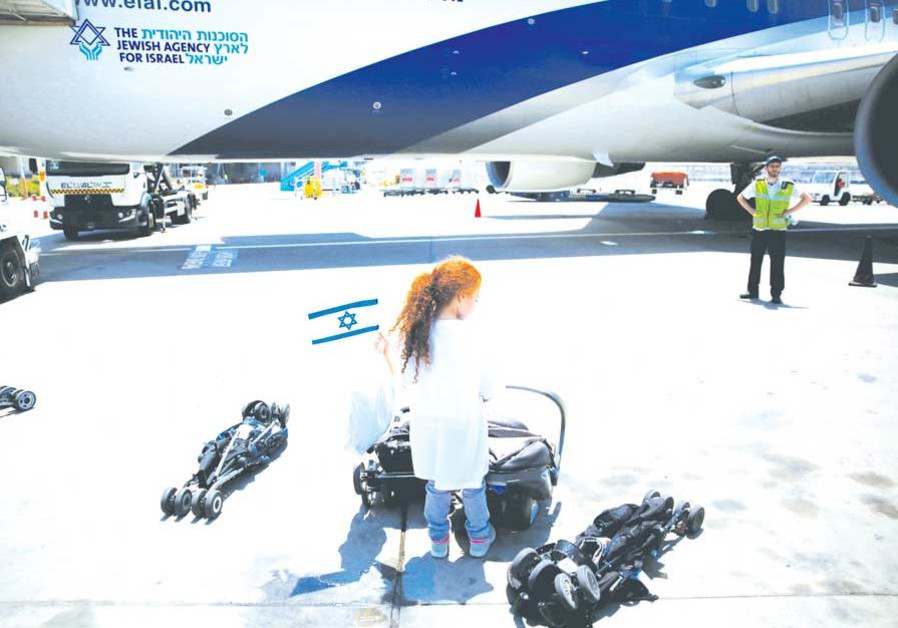 A YOUNG olah, newly arrived from France, waves an Israeli flag after disembarking from a plane upon