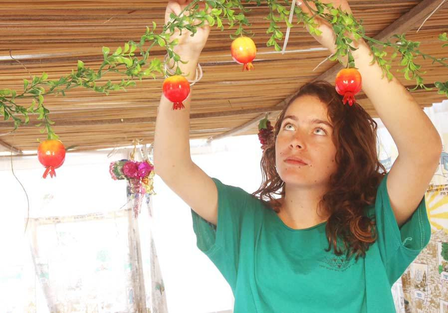 A WOMAN decorates her sukka ahead of the holiday.