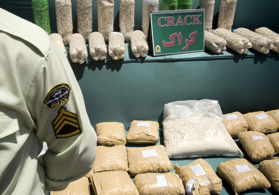 An Iranian anti-narcotics policeman stands guard beside a display of confiscated drugs