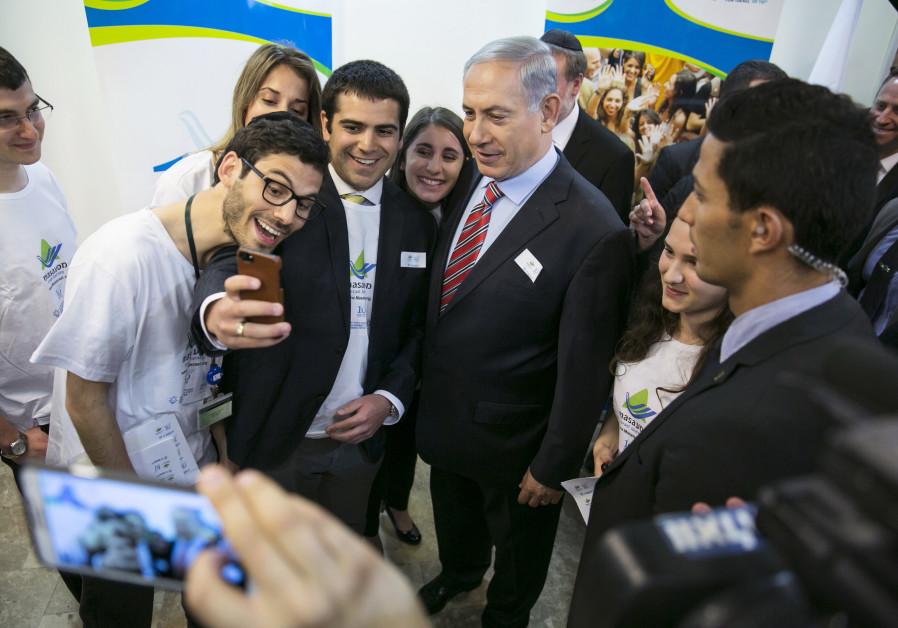 Israel's Prime Minister Benjamin Netanyahu (C) has his photo taken with members of Masa before atten