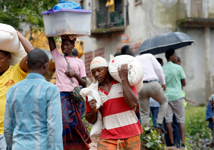 People carry away food and items in Regent town, Sierra Leone