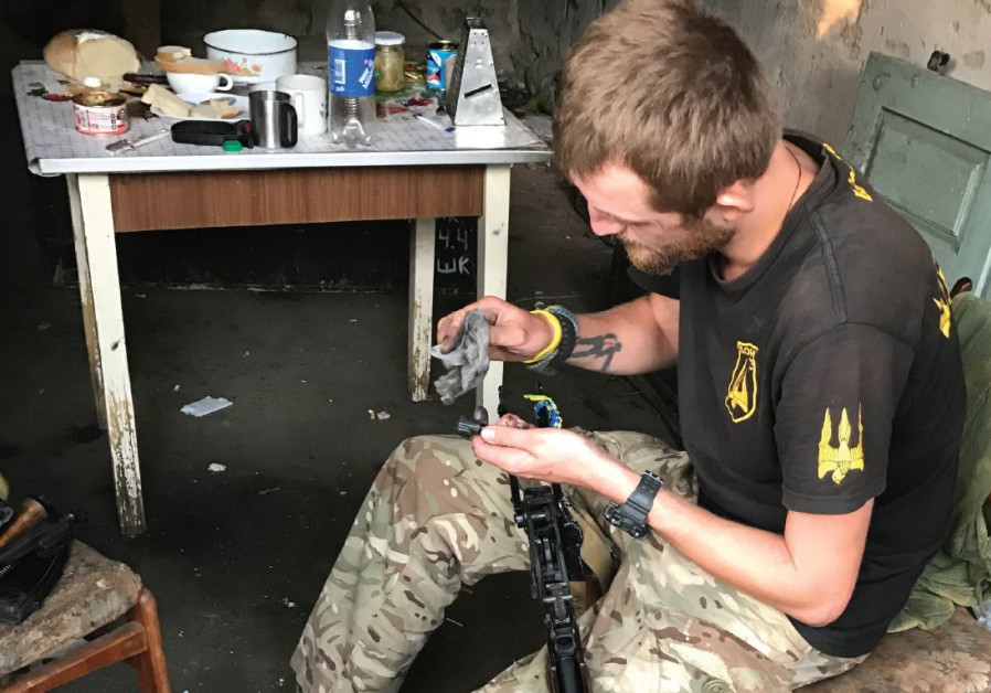 A Donbas volunteer cleans his rifle