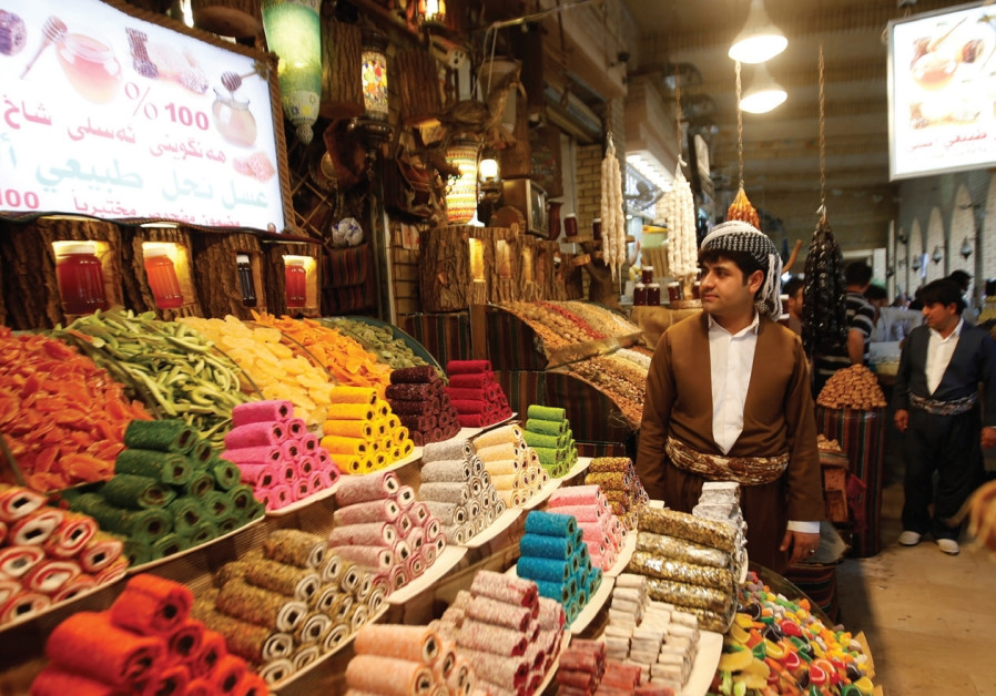 A KURDISH MAN sells sweets at a market in Erbil, the capital of Iraq's Kurdistan region.