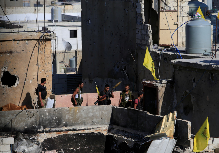 A Palestinian Fatah fighter holds a weapon inside the Ain el-Hilweh refugee camp near Sidon, souther