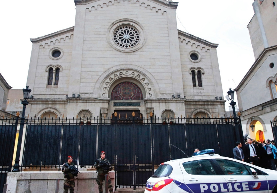 SOLDIERS AND a police car stand in front of a synagogue in Marseille, France.
