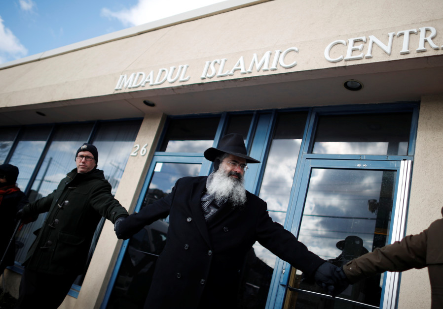 Jewish, Christian and Muslim worshippers form a 'ring of peace' outside an Islamic cultural centre