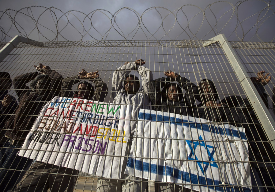 African migrants gesture behind a fence during a protest against Israel's detention policy towards t
