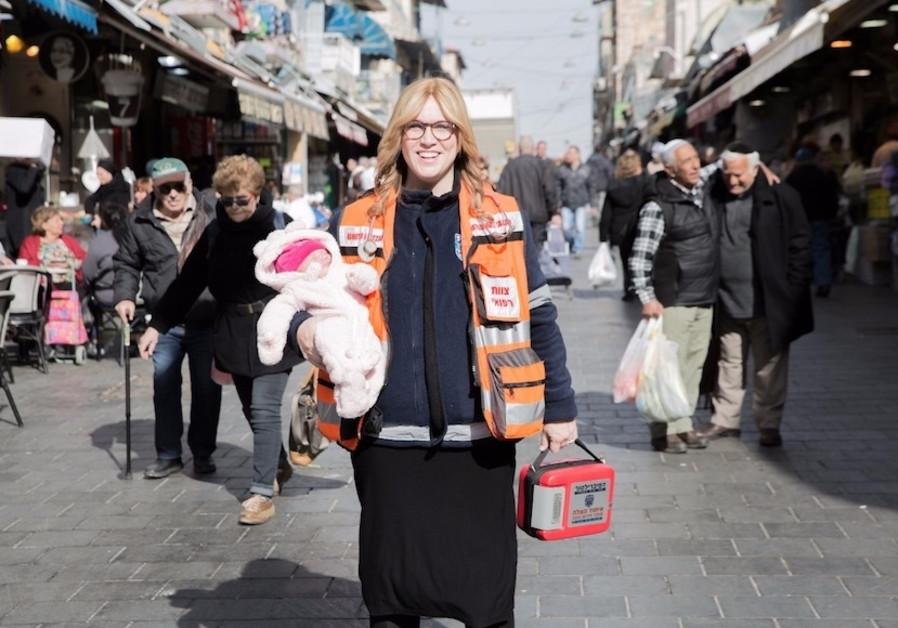 Miriam Ballin, holding her baby daughter, at the Mahane Yehuda market in Jerusalem.