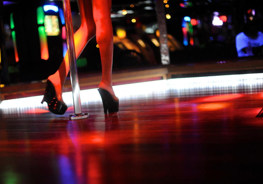 A dancer performs for customers at a strip club