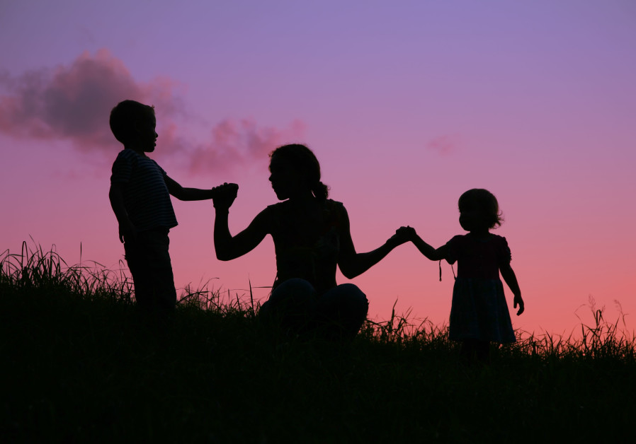 A mother holds two children by the hands during a sunset