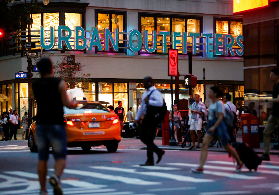 People crosses the street next to the Urban Outfitters store in Manhattan, New York