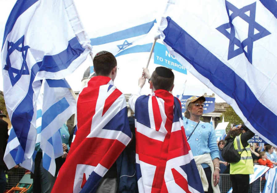 UK AND Israeli flags together at a march in London.