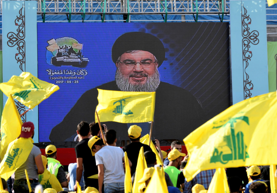 Hezbollah leader Sayyed Hassan Nasrallah speaks to supporters on a screen