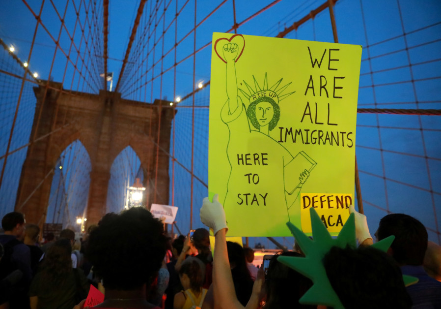 People march across the Brooklyn Bridge to protest the planned dissolution of DACA