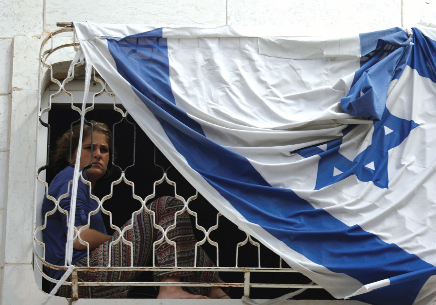 A YOUNG Jewish settler in Hebron looks out of a window in a disputed building.
