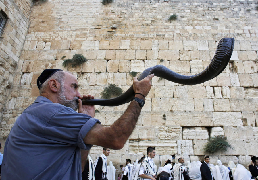 A Jewish worshipper blows a Shofar,  at the Western Wall ahead of Rosh Hashana