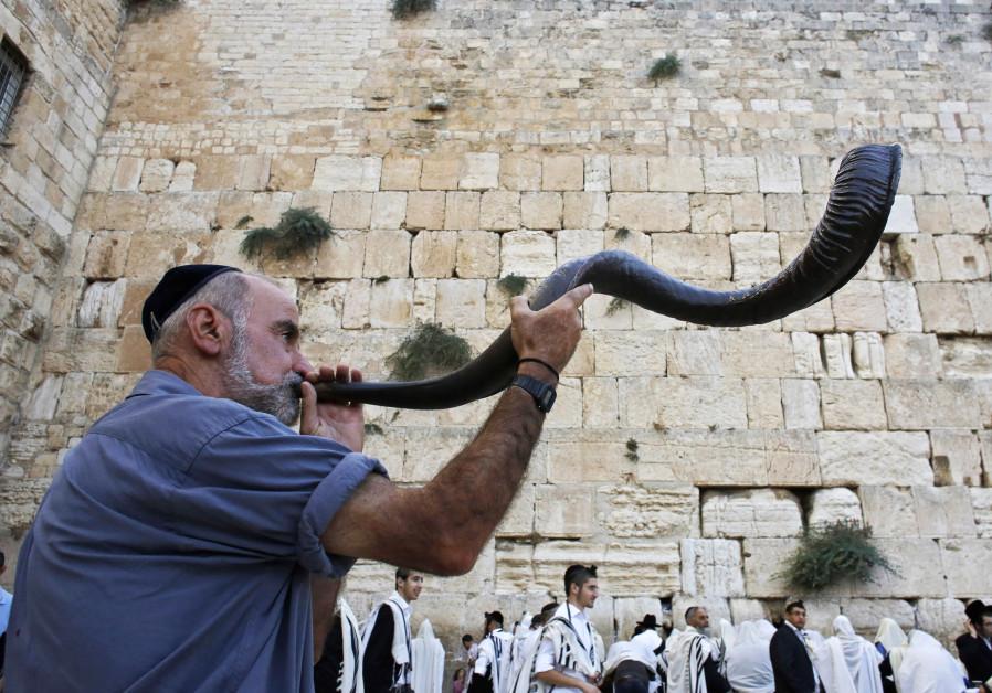 A Jewish worshipper blows a Shofar,  at the Western Wall ahead of Rosh Hashana