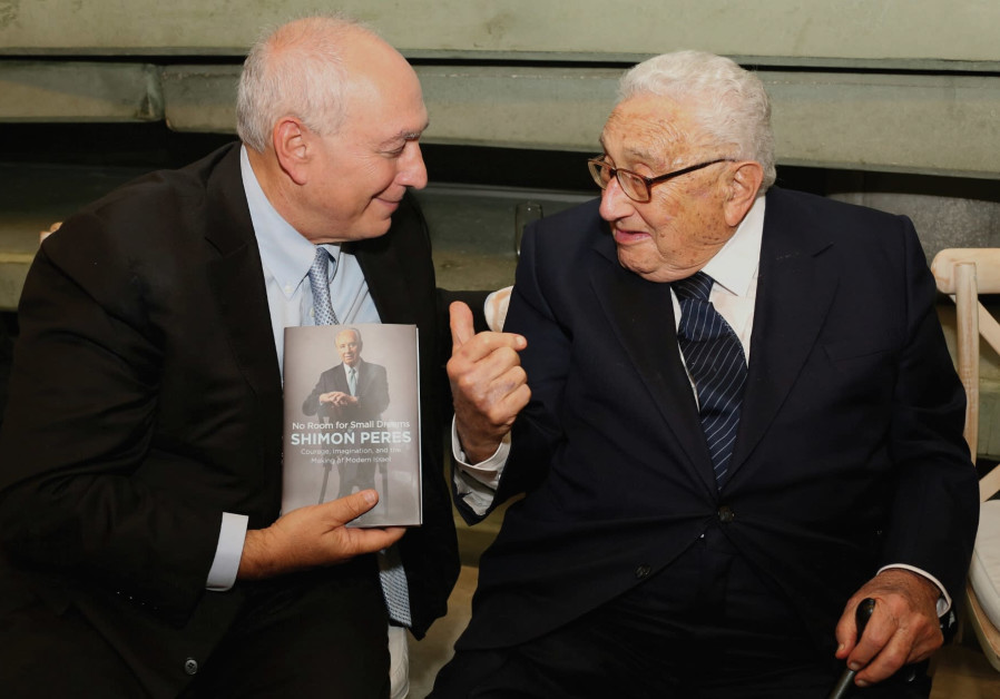 Chemi Peres (left) presents a copy of his father's autobiography to Henry Kissinger.
