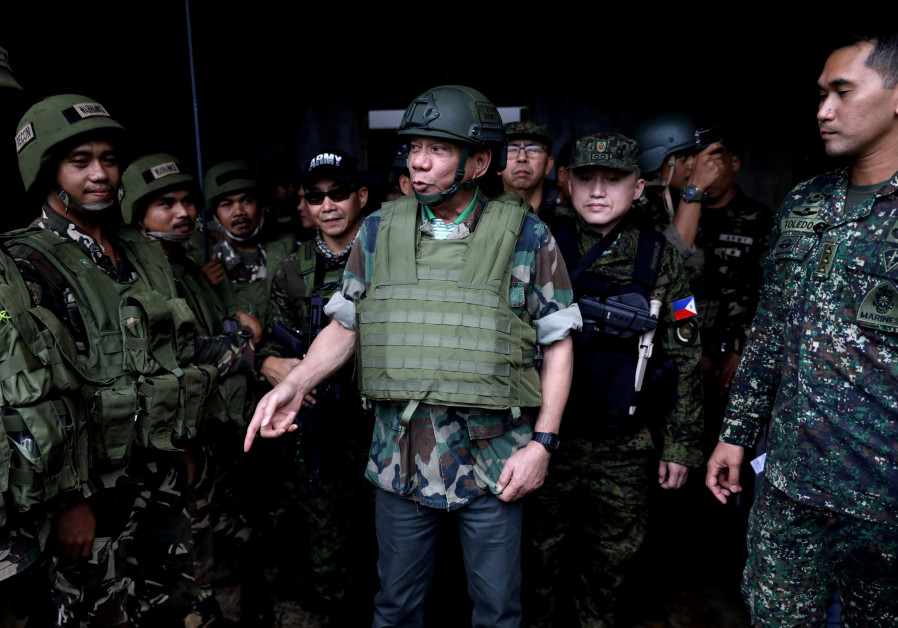 Philippine President Rodrigo Duterte wears a bulletproof vest and a helmet as he gives a pep talk t