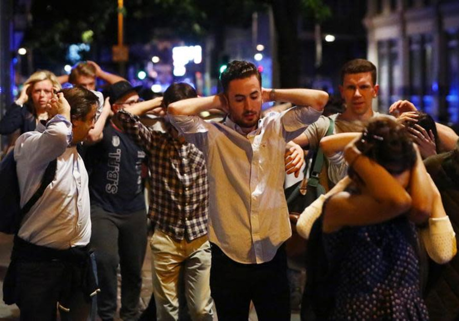 People leave the London Bridge area with their hands up after a terrorist attack
