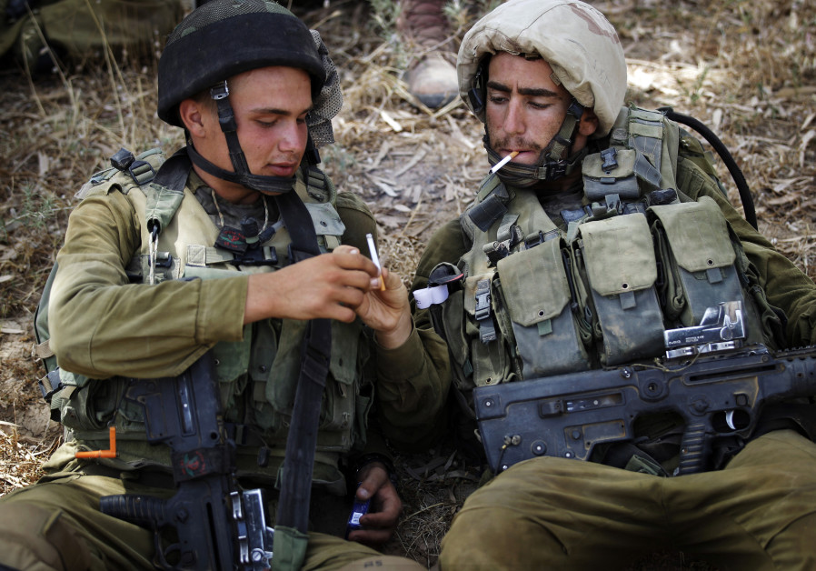 IDF soldiers share cigarettes while resting in the shade