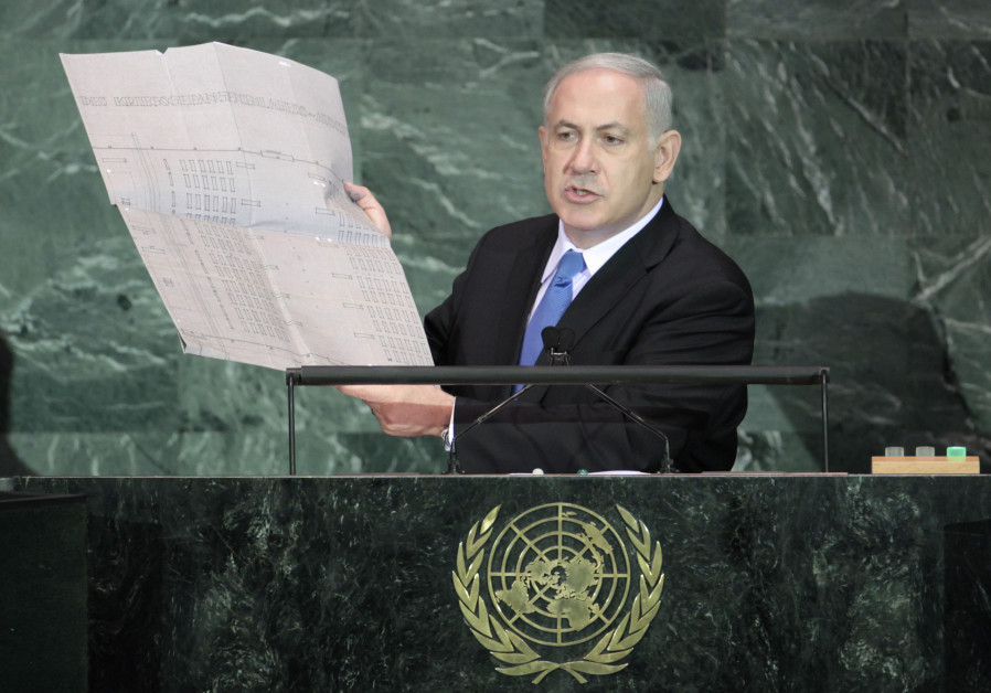 Israeli Prime Minister Benjamin Netanyahu holds up a document outlining plans for the Auschwitz deat