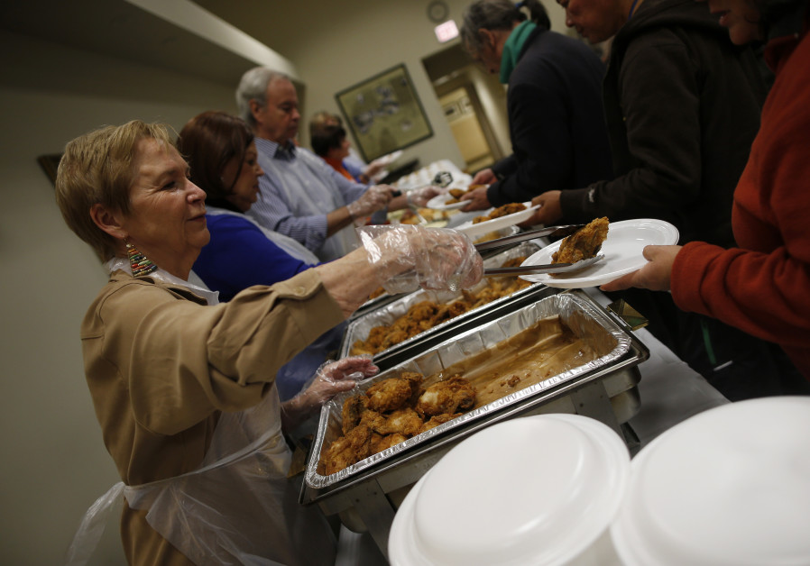 Volunteers serve people during a free dinner service