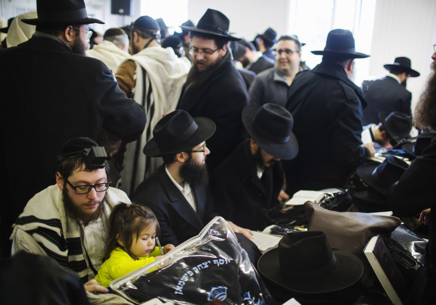 A young girl draws as she sits with a Rabbi praying at a Chabad-Lubavitch synagogue