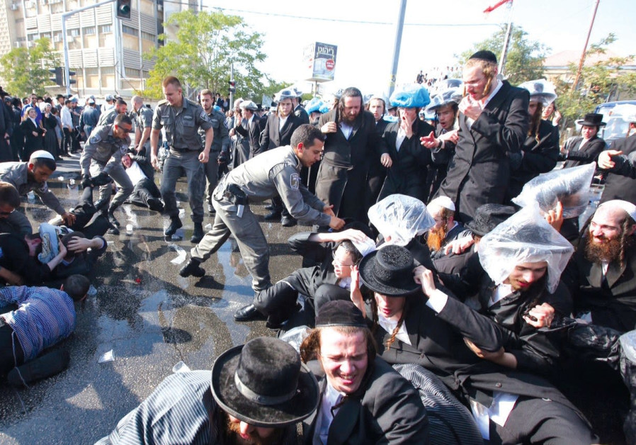 BORDER POLICE OFFICERS detain ultra-Orthodox protesters on Sunday during a draft riot in Jerusalem.