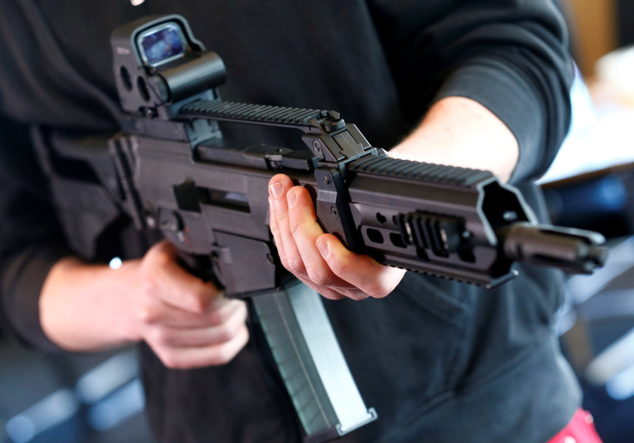A man holds a G 36 KA rifle manufactured by Heckler & Koch