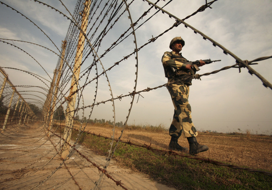 An Indian Border Security Forces soldier patrols near the fenced border with Pakistan