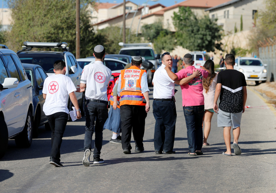 Medics and people at the scene where a Palestinian gunman killed three Israelis guards