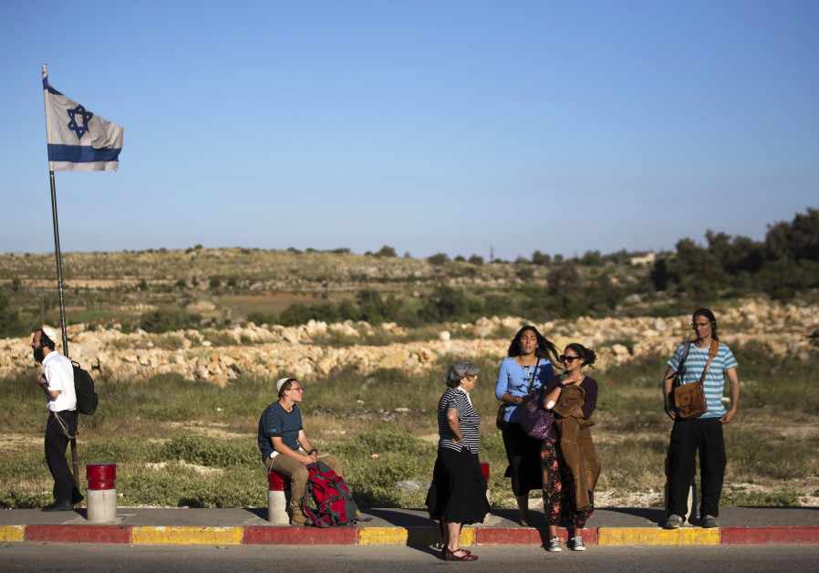 Israeli pedestrians stand on a roadside near the West Bank Jewish settlement of Efrat