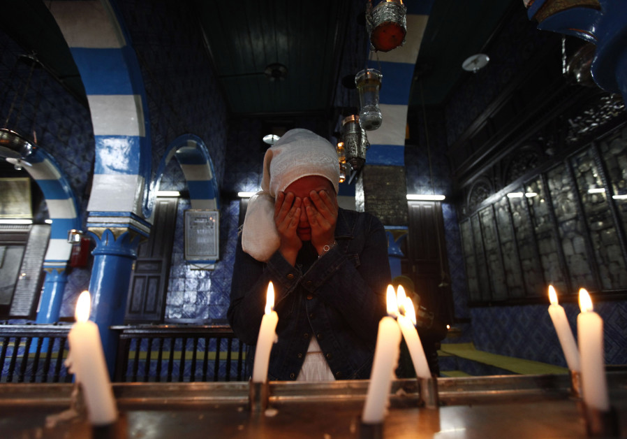 A Jewish woman lights candles during a pilgrimage to the El Ghriba synagogue in Djerba, Tunisia