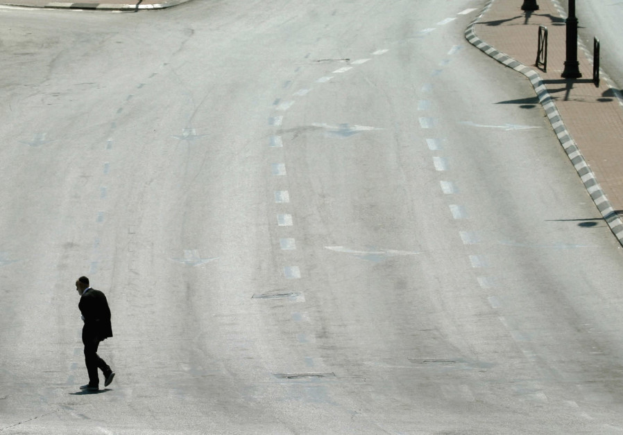 A MAN walks on an empty street in Jerusalem during Yom Kippur in this file photo from 2004.