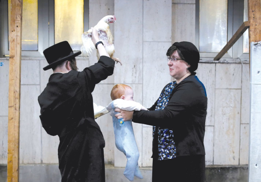 A HAREDI man holds a chicken over a baby as he performs the 'kapparot' ritual last year in Ashdod. M
