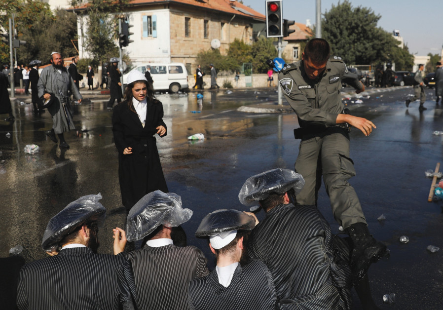 ULTRA-ORTHODOX MEN and police clash during a protest against serving in the Israeli army.